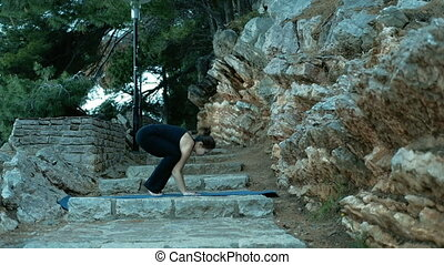 Young woman doing yoga in park on stone staircase on blue mat outside.