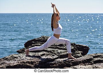 Young woman doing yoga in the beach