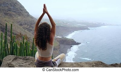 Young woman doing yoga in the mountains on an island overlooking the ocean sitting on a rock on top of a mountain meditating in Lotus position