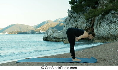 Young woman doing yoga near sea at sunset on blue mat outdoors.