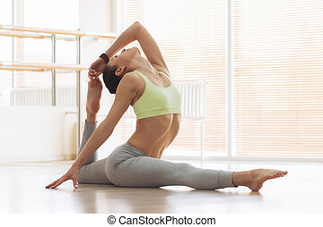 Young woman doing yoga on floor