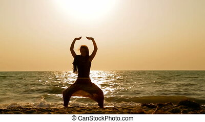 Young Woman Doing Yoga On Sandy Beach At Sunset