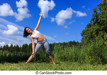 girl doing yoga outdoor looking in camera and smiling, ladscape