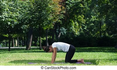 Young woman doing yoga pose on park