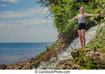 Young Woman doing Yoga Position Near a Waterfall
