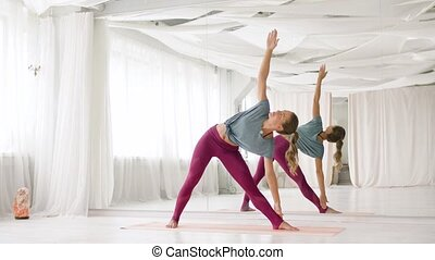 young woman doing yoga triangle pose at studio - fitness,...