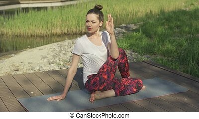 Young woman doing yoga twist in park