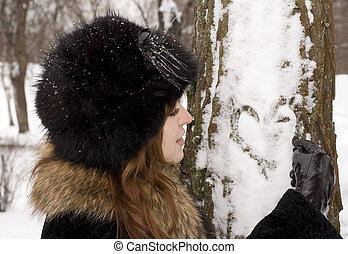 Young woman drawing heart on the tree in the winter park