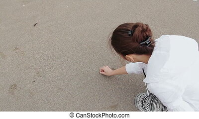 Young Woman Drawing Love On Sand