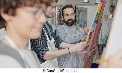 Young woman is drawing picture while helpful teacher is helping man with portrait in art school during creative enjoyable lesson. Hobby and occupation concept.