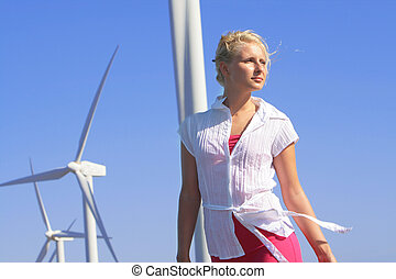 young woman dreams about the future on a wind farm beneath...
