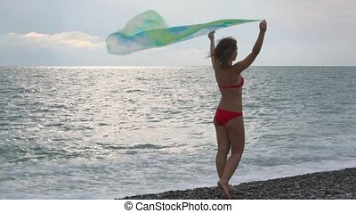 young woman dressed in bikini standing in beach with fabric in hands, back to camera