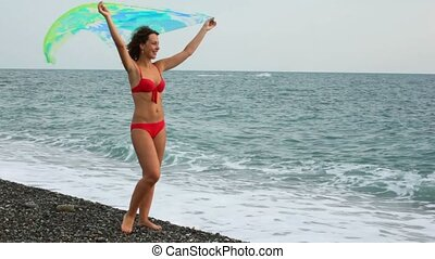 young woman dressed in bikini standing in beach with fabric in hands