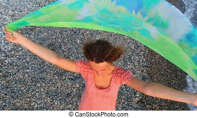 young woman dressed in bikini with fabric standing on beach, flying camera