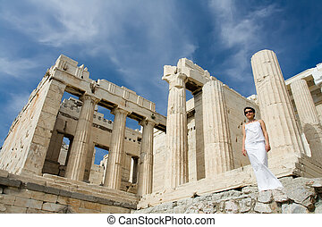 Young woman dressed white near the columns of entrance propylaea to ancient temple Parthenon in Acropolis Athens Greece on blue sky background