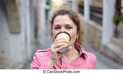 Young woman drink coffee outdoors - Woman holding coffee...