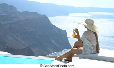 young woman drinking a cocktail enjoying a magnificent view of Santorini near the pool, Greece