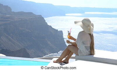 young woman drinking a cocktail enjoying a magnificent view...