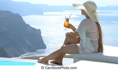 young woman drinking a cocktail enjoying a magnificent view of Santorini near the pool
