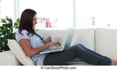 Young woman drinking a coffee in front of her laptop