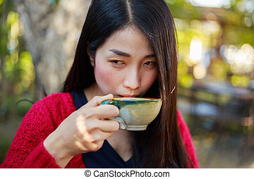 woman drinking a cup of coffe in the garden
