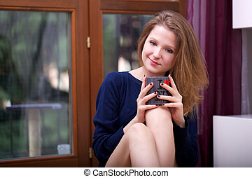 young woman drinking a cup of..
