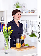 young woman drinking a glass of orange juice