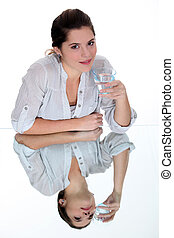 Young woman drinking a glass of water on a mirrored table