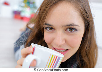 young woman drinking a hot cup of tea