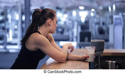 Young woman drinking a protein shake and looking at the...