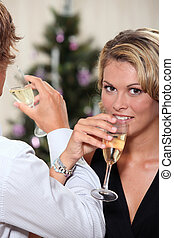 Young woman drinking champagne with her boyfriend at...