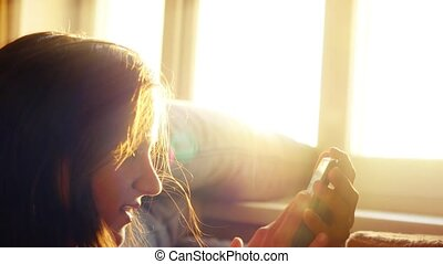 Young woman drinking coffee and sending messages with her...