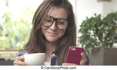 Young woman drinking coffee and sending messages with her mobile phone