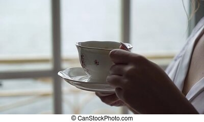 Young woman drinking coffee from cup in the morning. Breakfast at home