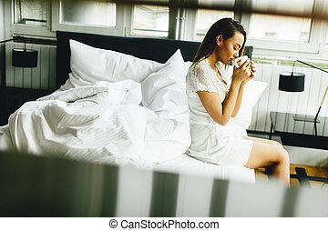 Young woman drinking coffee in the bed