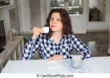 Young woman drinking coffee in the kitchen