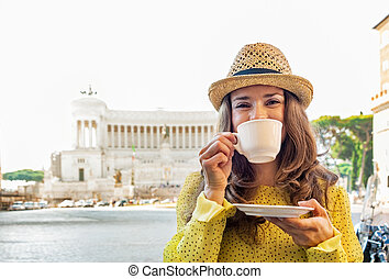 Young woman drinking coffee on piazza venezia in rome, italy