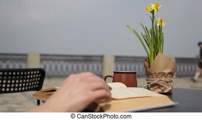 Young woman drinking coffee, reading an old book, leafing through the pages at a table in a street cafe, enjoying the view of the sea