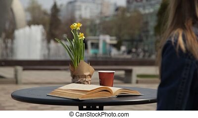Young woman drinking coffee, reading an old book, leafing through the pages at a table in a street cafe, enjoying the view of the fountain