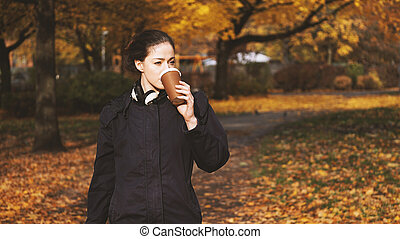 young woman drinking coffee to go while on the move