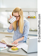Young woman drinking coffee while studying in kitchen