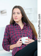 young woman drinking coffee with thoughtful expression on her face