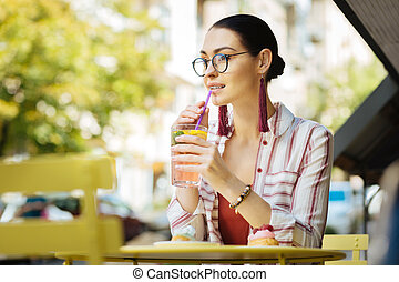 Young woman drinking cold lemonade and touching a sipping straw