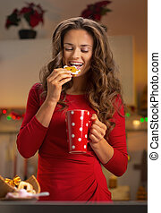 Young woman drinking cup of hot chocolate with christmas cookies