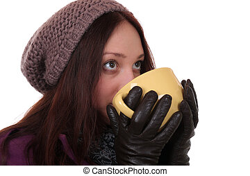 Young woman drinking cup of tea in winter and looking up