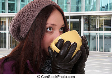 Young woman drinking cup of tea in winter outdoors in town