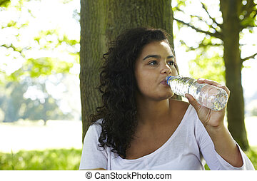 Young Woman Drinking From Bottle Of Water