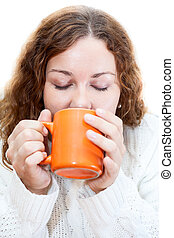 Young woman drinking from orange mug, isolated on white background