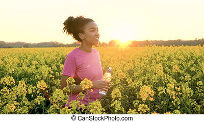 Young woman drinking from water bottle after running or jogging in field of yellow flowers