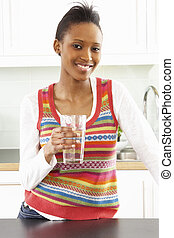 Young Woman Drinking Glass Of Water In Modern Kitchen